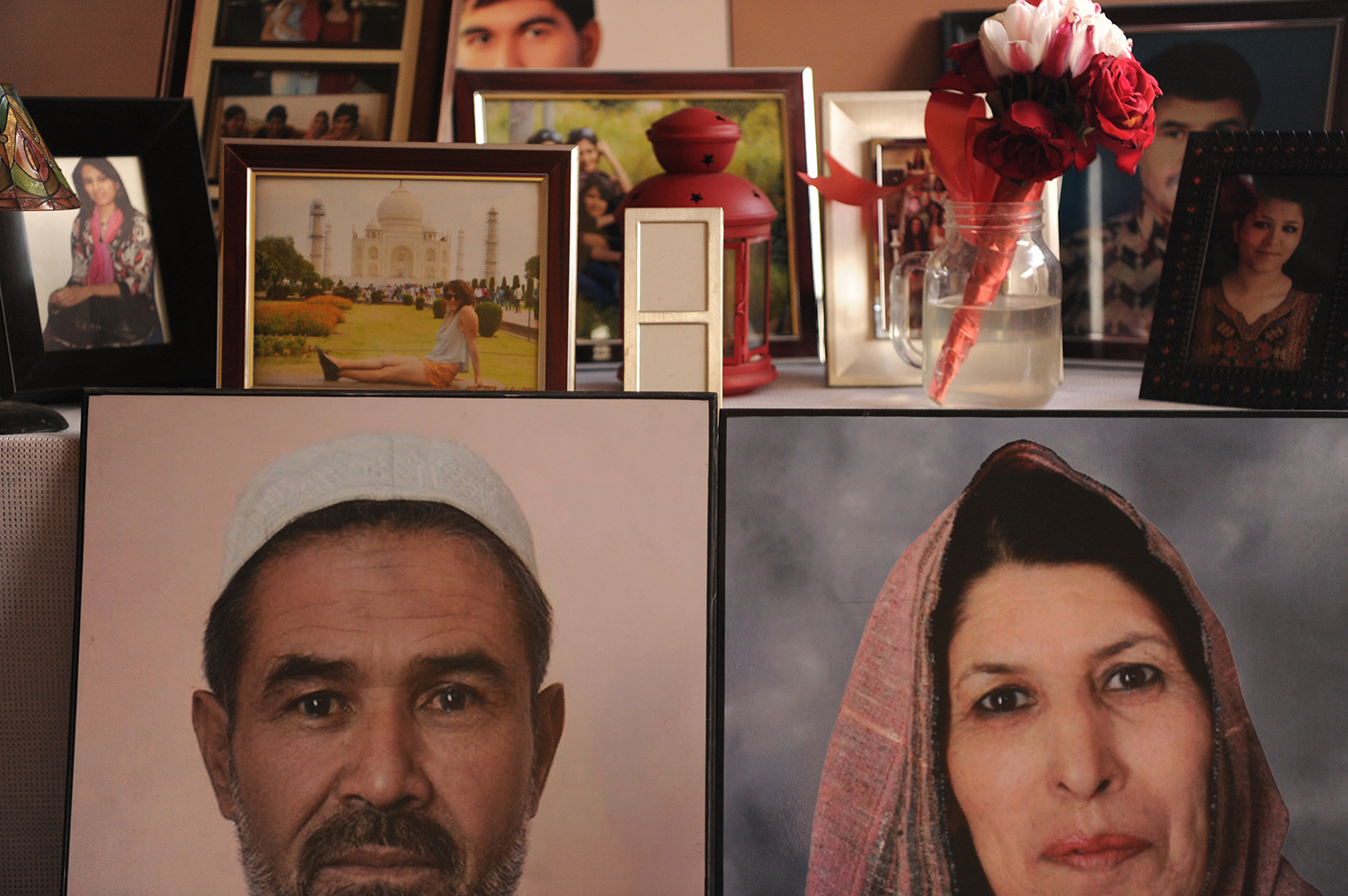 This photo shows pictures of 22-year-old Mubareka Sahar Fetrat, her parents in her bedroom in Kabul, Afghanistan, March 26, 2018. At the age of 21 Fetrat lost both her parents between January and August of 2017. © Farzana Wahidy
