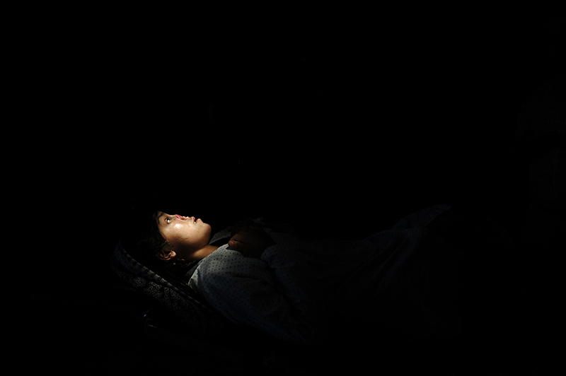 Lying in a hospital operation bed to get her treatment the 20 years old Rezagul whose nose was cut by her husband asks for justice and help, January 2016. © Farzana Wahidy