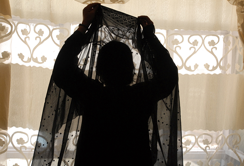 An unidentified Afghan sex worker fixes her headscarf to cover her face while being photograph in her Madameís house in Kabul, Afghanistan, 2008. © Farzana Wahidy